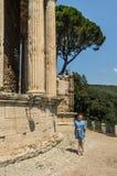 La muchacha encantadora camina cerca de las ruinas del templo de la diosa Vesta en Tivoli, Italia imagen de archivo libre de regalías
