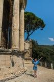 La muchacha encantadora camina cerca de las ruinas del templo de la diosa Vesta en Tivoli, Italia fotos de archivo libres de regalías