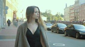 La muchacha encantadora en un mono de moda del cóctel va a lo largo de una calle de la ciudad en el slo-MES metrajes