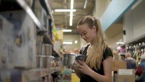 La muchacha encantadora está mirando las cacerolas en una ferretería, sosteniendo dos en manos almacen de metraje de vídeo