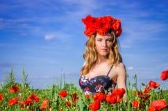 La muchacha encantadora joven camina en el campo con las amapolas florecientes con una guirnalda de amapolas en su cabeza Fotos de archivo