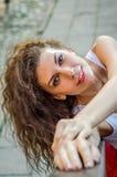 La muchacha encantadora joven con los ojos rizados y sonrisa hermosa, está confiando en la verja de la escalera en una fortaleza  Foto de archivo libre de regalías