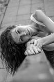 La muchacha encantadora joven con los ojos rizados y sonrisa hermosa, está confiando en la verja de la escalera en una fortaleza  Imagen de archivo libre de regalías