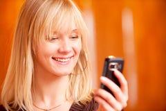 La muchacha encantadora lee sms Fotografía de archivo libre de regalías