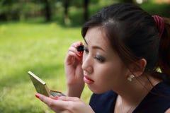 La muchacha encantadora mira en espejo contra parque verde Fotografía de archivo libre de regalías