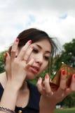 La muchacha encantadora mira en espejo en el parque Fotos de archivo