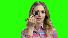 La muchacha encantadora pone maquillaje en la pantalla verde metrajes