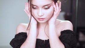 La muchacha encantadora se sostiene la cara con sus manos y hace sus ojos estrechos, la princesa encantó en una muñeca linda, ves almacen de video