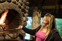 La muchacha enciende el fuego en chimenea foto de archivo libre de regalías