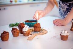 La muchacha enciende la vela, adorna las magdalenas de la celebración del Año Nuevo, molletes del chocolate en la tabla foto de archivo libre de regalías