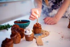 La muchacha enciende la vela, adorna las magdalenas de la celebración del Año Nuevo, molletes del chocolate en la tabla imagenes de archivo