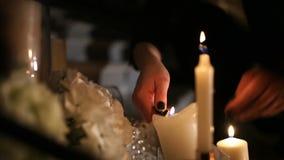 La muchacha enciende las velas de la decoración en la oscuridad Cierre para arriba