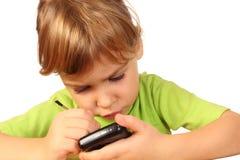La muchacha encontró algo interesante en teléfono Fotos de archivo
