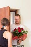 La muchacha encuentra al novio con las flores cerca de la puerta Fotografía de archivo libre de regalías