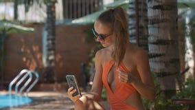 La muchacha endereza corte de pelo sostiene el teléfono al lado de la piscina casera