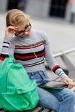 La muchacha endereza los vidrios que se sientan en banco con Tablet PC Imagen de archivo libre de regalías
