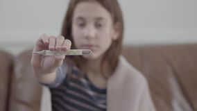 La muchacha enferma cansada del retrato se sienta en sofá y mostrar un termómetro en la cámara Concepto de un ni?o enfermo Medici almacen de metraje de vídeo