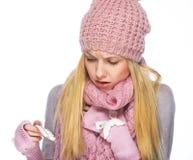 La muchacha enferma del adolescente en sombrero del invierno y la bufanda que mira en píldoras embalan Imagen de archivo