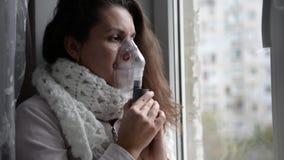 La muchacha enferma hace la inhalación con una máscara en su cara almacen de metraje de vídeo