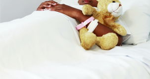 La muchacha enferma que descansa con el peluche refiere la cama almacen de metraje de vídeo