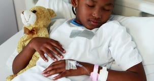 La muchacha enferma que descansa con el peluche refiere la cama almacen de video