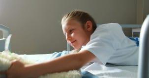 La muchacha enferma que juega con el peluche refiere la cama almacen de metraje de vídeo