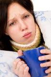 La muchacha enferma que miente en la cama, té de consumición Imagen de archivo libre de regalías