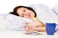 La muchacha enferma que miente en la cama, té de consumición Imagenes de archivo