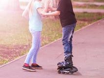 La muchacha enseña al muchacho a montar en pcteres de ruedas en la puesta del sol foto de archivo libre de regalías