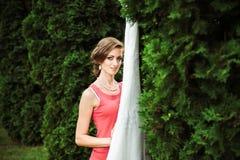 La muchacha entre los árboles acerca a su vestido de boda blanco fotografía de archivo libre de regalías
