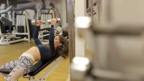 La muchacha entrena en el gimnasio con pesas de gimnasia, ella entrena a los músculos de la parte posterior y de manos almacen de video