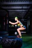 La muchacha entrena a los músculos de sus piernas en el gimnasio que salta en un neumático grande Se divierte concepto de la form fotos de archivo libres de regalías