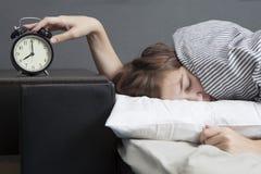 La muchacha, envuelta en una manta rayada, pone hacia fuera su mano para apagar la alarma Hay ocho horas en el despertador fotografía de archivo libre de regalías