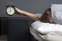 La muchacha, envuelta en una manta rayada, pone hacia fuera su mano para apagar la alarma Hay ocho horas en el despertador imagen de archivo