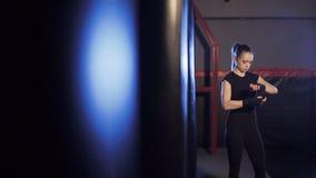 La muchacha envuelve los vendajes en sus manos en el gimnasio del boxeo almacen de video