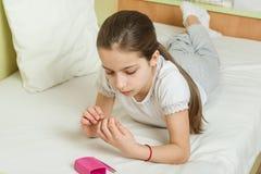 La muchacha es 10 años en casa en la cama en su ropa casera, clava sus clavos usando los accesorios de la manicura Fotos de archivo