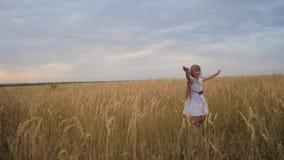 La muchacha es adolescente, se separó los brazos como las alas y los funcionamientos a través del campo Cámara lenta metrajes