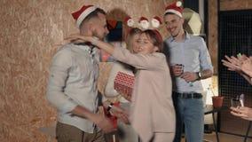 La muchacha es de agradecimiento y de abrazo de sus colegas para el regalo de la Navidad en partido en oficina almacen de video