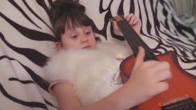 La muchacha es de mentira y que toca una guitarra del ` s del niño metrajes