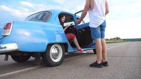 La muchacha es el salir de auto retro y del funcionamiento lejos con su novio El hombre joven abre la puerta del coche viejo para almacen de video