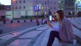 La muchacha es emocional, los trabajos en la tableta, por la tarde en el centro de ciudad almacen de video
