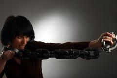 La muchacha es encadenamiento del metal de la explotación agrícola Imagenes de archivo