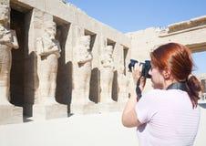 La muchacha es fotografía las estatuas antiguas en Karnak Fotos de archivo