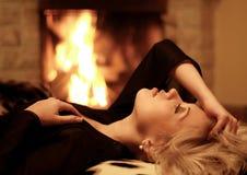 La muchacha es heated en una chimenea Imagenes de archivo