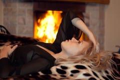 La muchacha es heated en una chimenea Fotos de archivo libres de regalías