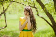 la muchacha es hermosa por el árbol En fotografía de archivo