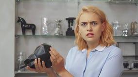La muchacha es infeliz con el precio de las colocaciones de los muebles para la casa almacen de video