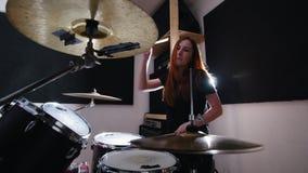 La muchacha es juegos muy emocionales del batería los tambores en el estudio almacen de video