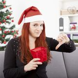 La muchacha es realmente infeliz con la caja de regalo para la Navidad Imagen de archivo libre de regalías