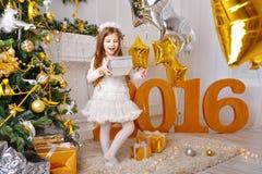 La muchacha es regalos felices por el Año Nuevo 2016 Fotografía de archivo